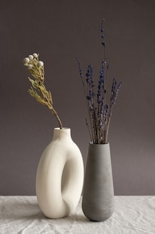 布で覆われたテーブルの上に互いに近くに立っている内部の乾燥した野花と白と黒の色の2つの手作りのセラミック花瓶