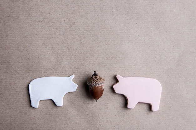 Two handmade clay pigs with acorn on craft paper background, valentine's day card or poster design elements.
