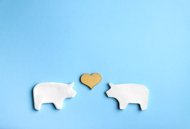 Two handmade clay pigs with small wooden heart on soft pastel background, valentine's day card or poster design elements.