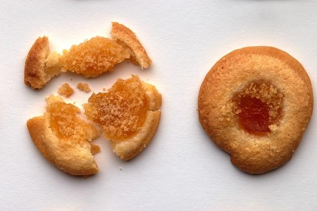 살구 잼이 균등하게 배열 된 수제 쿠키 2 개. 흰색 배경에 고립