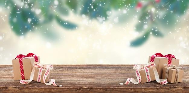 Две подарочные коробки ручной работы на деревянном столе с веткой падуба с листьями и ягодами un background