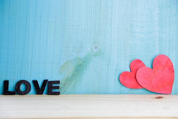 Два сердца ручной работы на деревенском деревянном фоне. концепция любви.