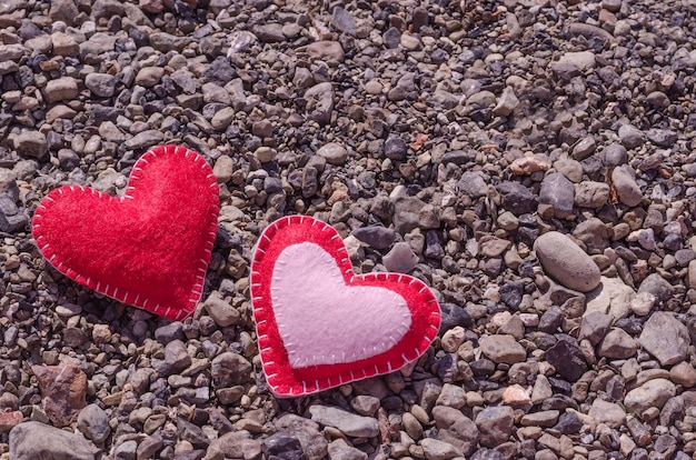 コピースペースのある小石のある夏のビーチの2つの手作りの心