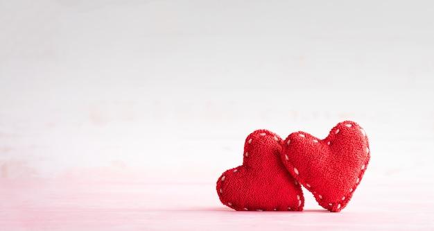 Два красных сердца ручной работы на ярком деревянном фоне. концепция дня святого валентина