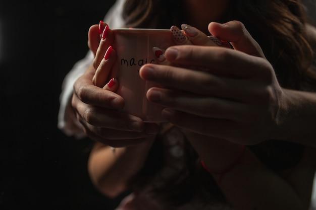 両手にホットコーヒーのマグカップ。