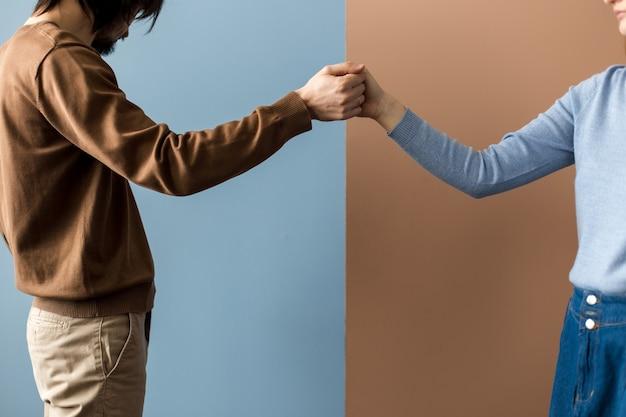 Две руки держатся кончиками пальцев в замке на разном фоне.