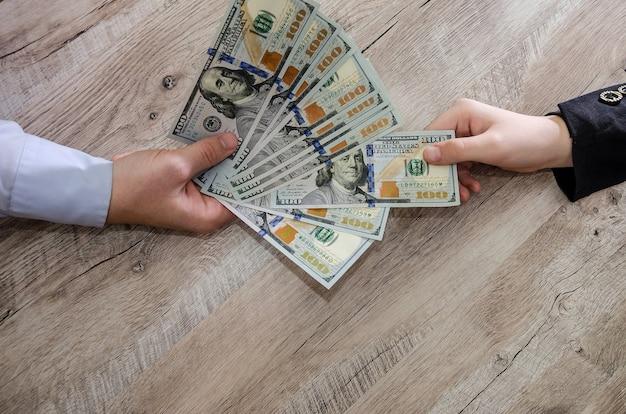 Две руки проходят долларовые банкноты