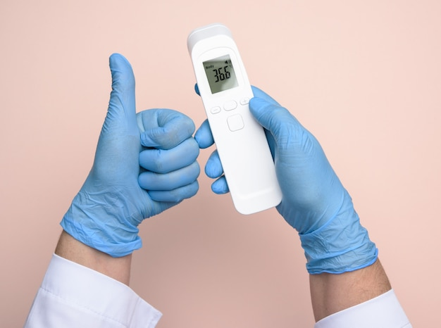 Two hands in blue latex gloves hold an electronic thermometer to measure temperature, non-contact device