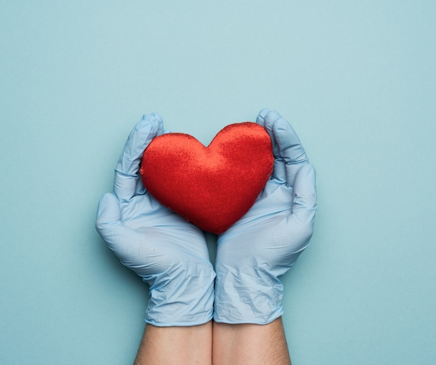 Two hands in blue latex gloves holding a red textile heart, donation concept, close up