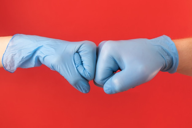 Two hands in blue medical gloves hold their fists, like a greeting. concept protection from a virus, pandemic, epidemic, disease. minimalism, copyspace. male and female hand.