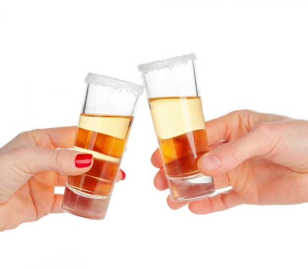 Two hands clinking glasses with shot cocktail isolated on white