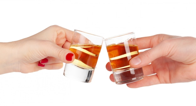 Two hands clinking shots of alcoholic beverage together