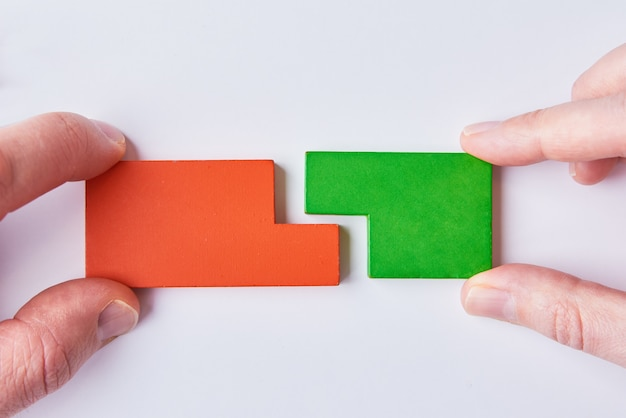 Two hands connect puzzle pieces on white