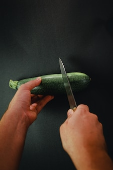 長いナイフでキュウリを切る2つの手