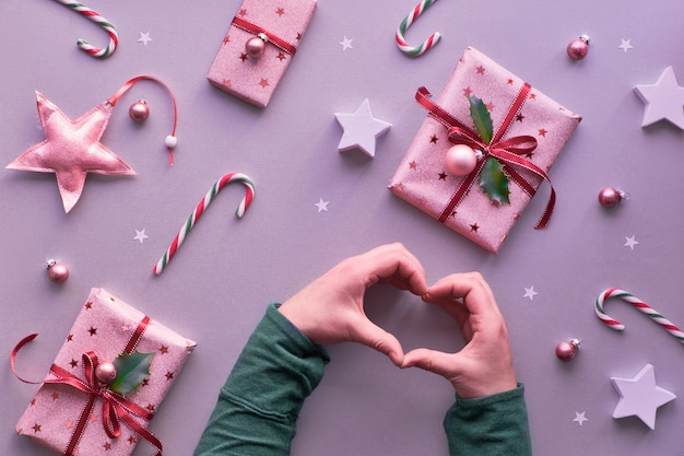 Two hands forming a heart shape on festive christmas background with pink wrapped gift boxes, candy canes, trinkets and decorative stars, geometric creative flat layout