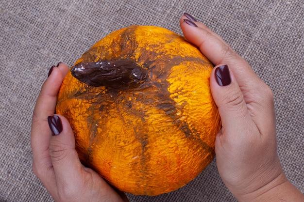 両手で自家製のオレンジ色の張り子のカボチャを黄麻布の表面にハロウィーン用に持ち、上面図