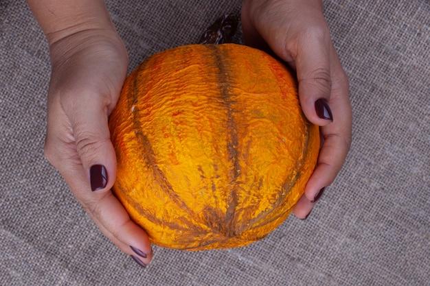 黄麻布の表面にハロウィーン用の自家製オレンジ張り子のカボチャを両手で持ちます