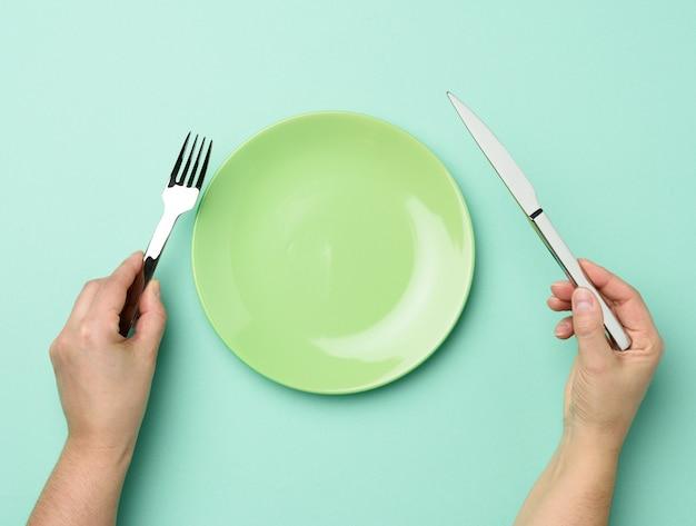 Две руки держат металлический нож и вилку на поверхности круглой пустой зеленой тарелки, вид сверху