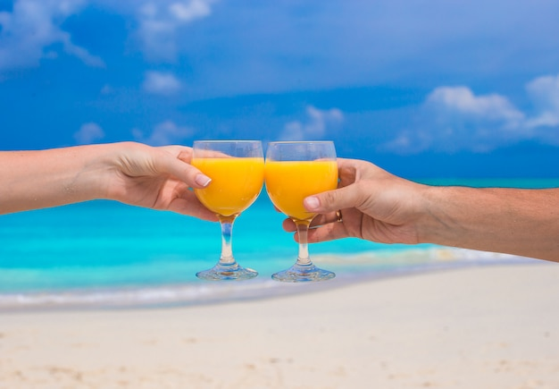 Two hands hold glasses with orange juice background blue sky