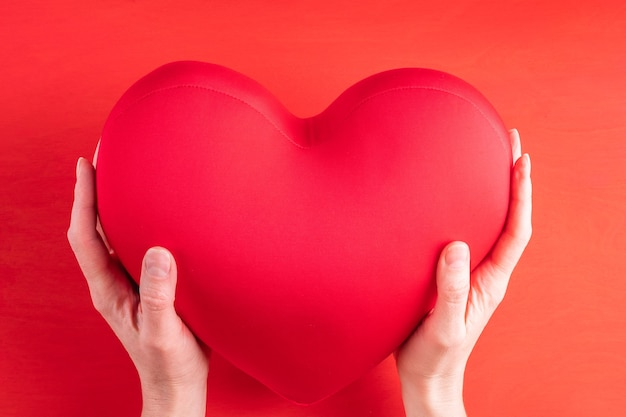 Two hands hold a large red heart-shaped pillow a symbol of love, relationships, friendship on a bright red background, close-up. valentine's day gift