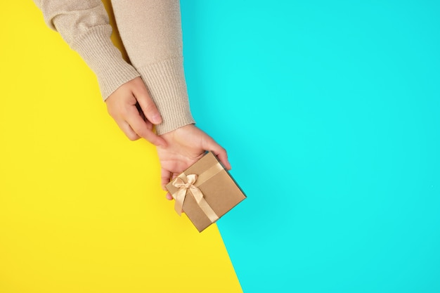 Two hands hold a paper closed golden box