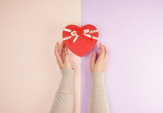 Two hands hold a paper closed red box in the shape of a heart