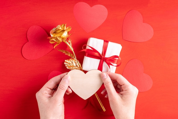 Two hands hold a wooden heart shape over a gift and a yellow gold rose symbol of love, relationships, family on a bright red background with copy space, close-up. valentine's day gift