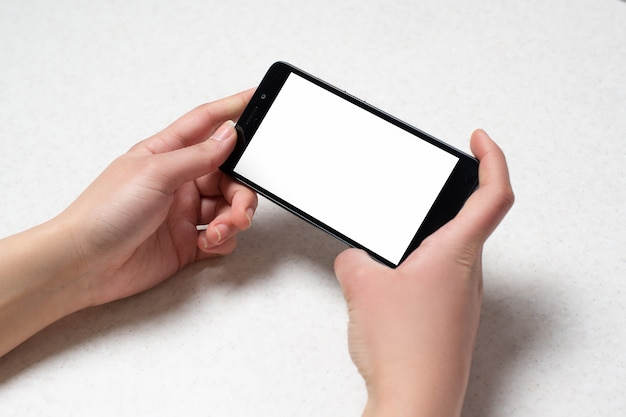 Two hands holding black phone on white wall