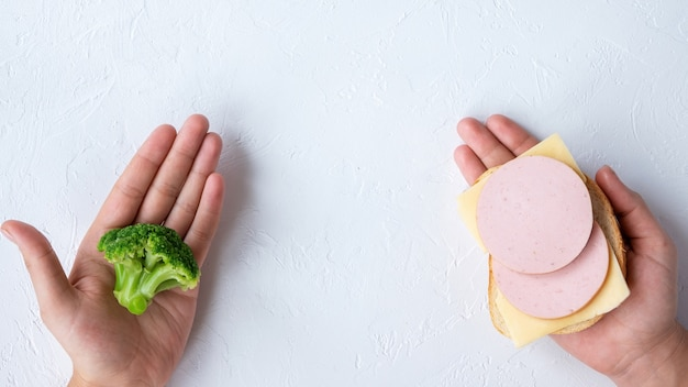 Two hands holding broccoli and a sandwich. healthy food idea. light background