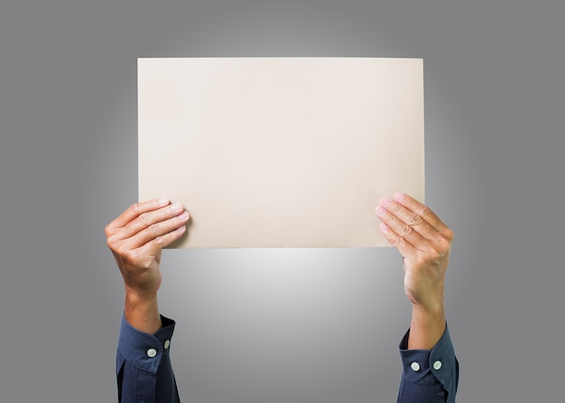 Two hands holding brown paper cardboard overhead with gray background