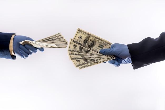 Две руки держат или дают доллар сша в медицинских перчатках для защиты, карантинный период covid19