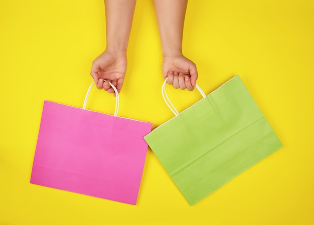 Two hands holding paper shopping bags on a yellow background