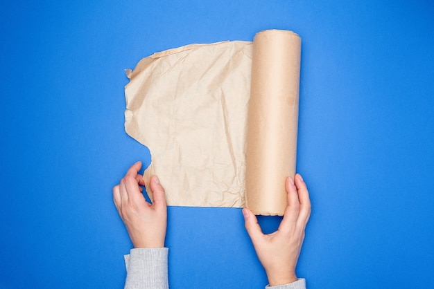 Two hands holding a roll of brown parchment paper on a blue surface