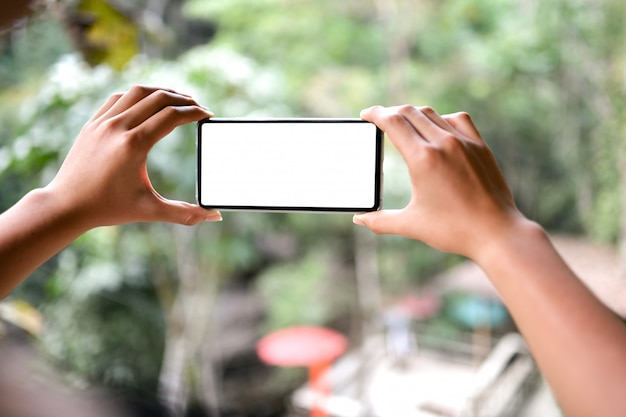 Two hands holding a smartphone blank screen with nature blurred view background.