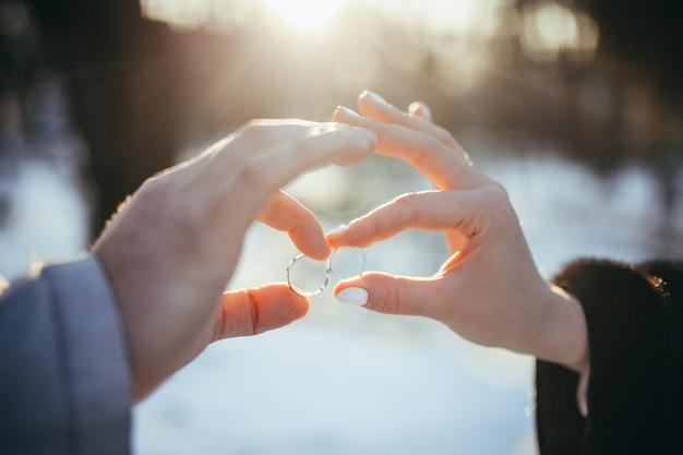 Две руки держат обручальные кольца зимой