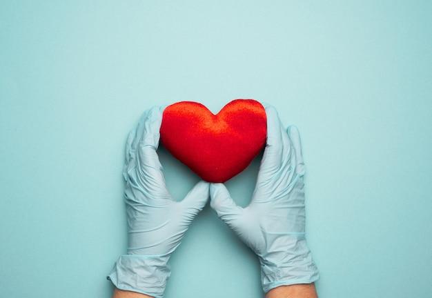 Две руки в синих латексных перчатках держат красное текстильное сердце, концепция пожертвования, крупным планом
