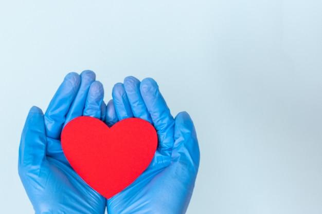 青い背景に赤いハートの形を保持している医療用青い手袋の両手、コピースペース。愛、健康の概念。