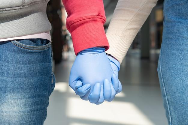 Две руки в резиновых перчатках, держа друг друга.