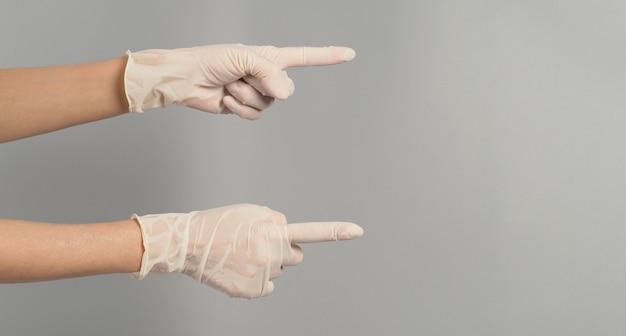 두 손이 가리키고 회색 배경에 의료용 장갑을 끼고 있습니다.