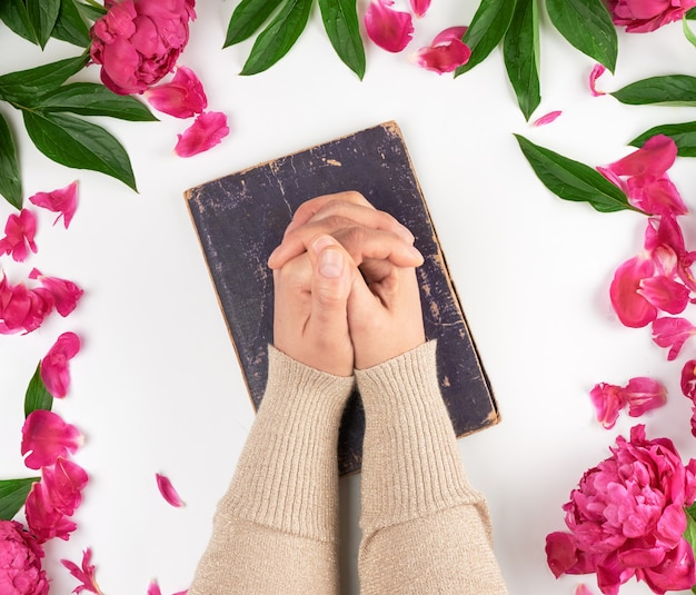 Two hands lie on the old book in a gesture of prayer