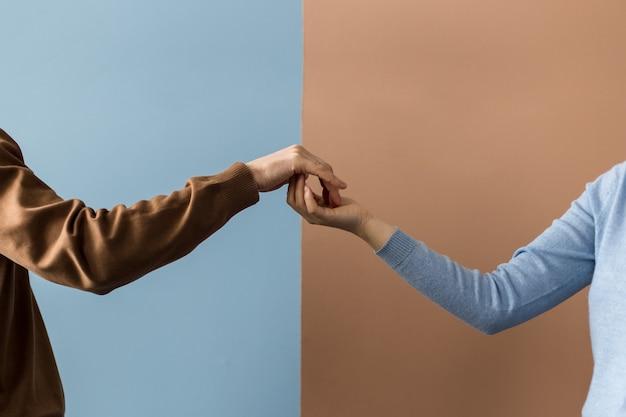 Две руки сливаются кончиками пальцев в кулак на разном фоне.