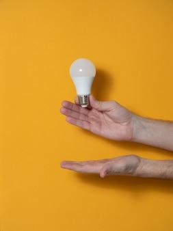 革新と創造的なコンセプトのための電球を握って男の2つの手。