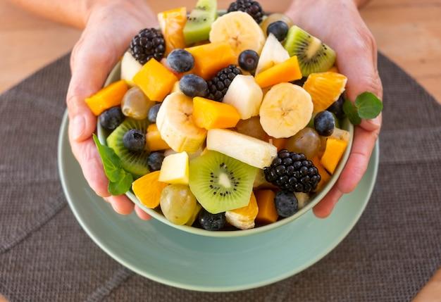新鮮なフルーツサラダでいっぱいのプレートを持っている高齢者の両手-健康的な食事の概念の老人引退した男