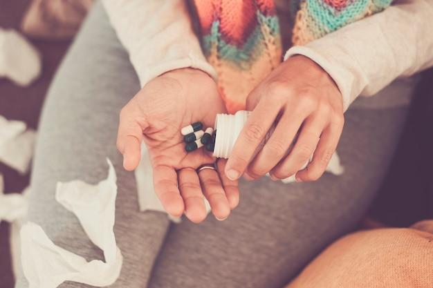 열이 있는 피곤한 여성의 두 손은 더 나은 상태를 유지하고 훌륭한 건강을 유지하기 위해 많은 약을 복용합니다.
