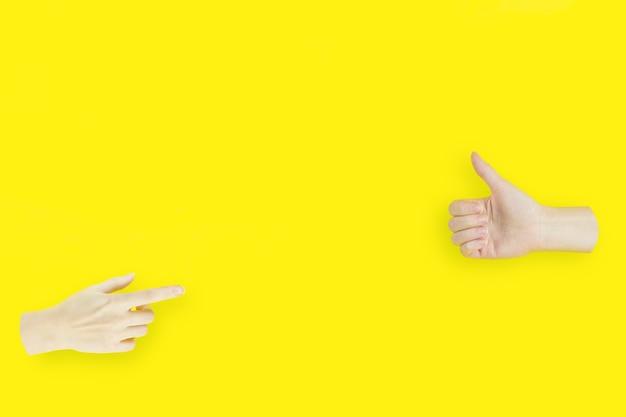 2つの手、1つは親指を立てるサインを示す手に人差し指を向けています。
