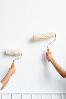Two hands painting the wall