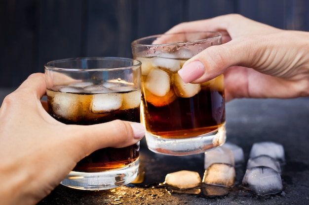 Two hands at a party holding glasses of whiskey with cola and ice