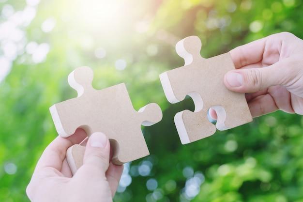 Человек 2 рук пытается соединить кусок головоломки бумаги пары белый с предпосылкой дерева свежей.