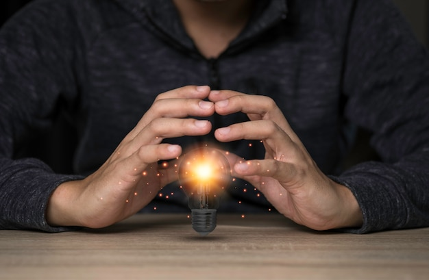 Two hands protecting the light bulb that is illuminating on the table