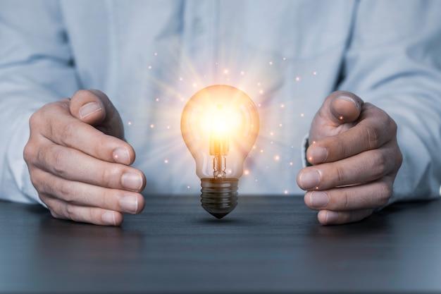 Две руки, защищая лампочку, которая горит на столе. творческая концепция защиты патентов и идей.